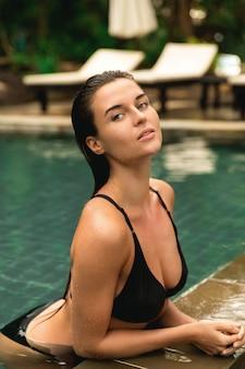 Mulher bonita relaxante na piscina