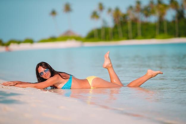 Mulher bonita relaxante na praia tropical de areia branca