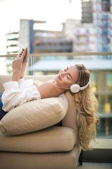 Mulher bonita relaxante na varanda, ouvindo música com fones de ouvido