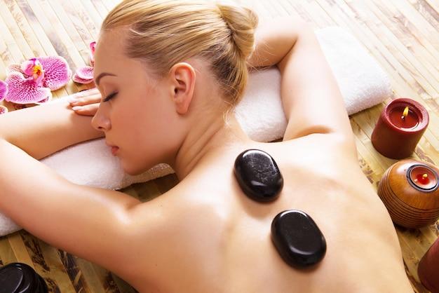 Mulher bonita relaxante no salão spa com pedras quentes no corpo. terapia de tratamento de beleza