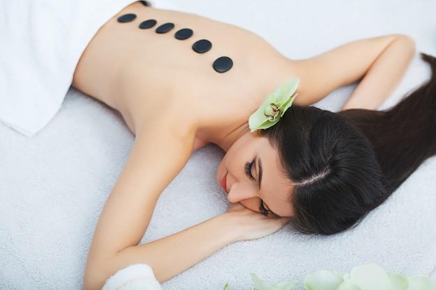 Mulher bonita relaxante no salão spa com pedras quentes no corpo.