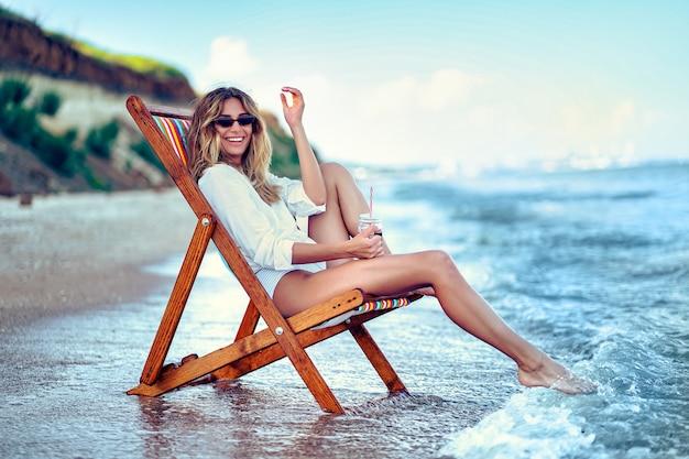 Mulher bonita relaxante numa praia espreguiçadeira e bebe água com gás