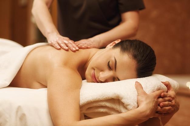 Mulher bonita relaxante recebendo massagem corporal no centro de bem-estar