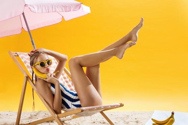 Mulher bonita relaxante sob o guarda-chuva com frutas
