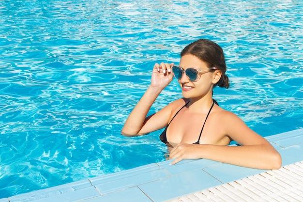 Mulher bonita relaxingin piscina de água em óculos de sol.