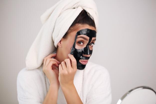 Mulher bonita remove uma máscara de limpeza do rosto