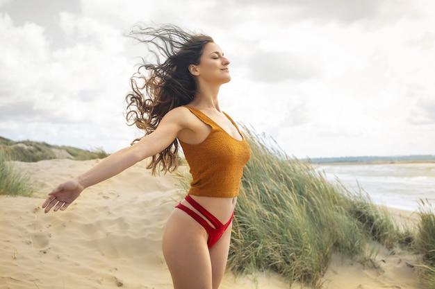 Mulher bonita, respirando profundamente, enquanto relaxa na praia