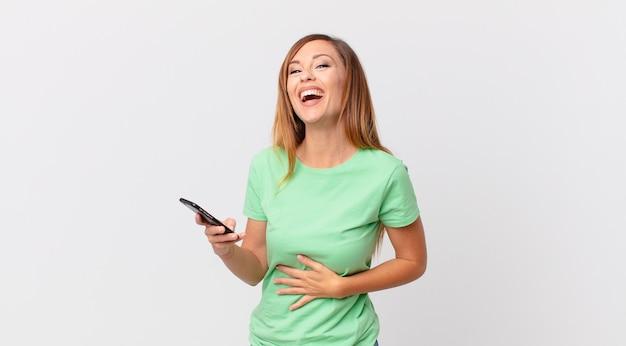 Mulher bonita rindo alto de uma piada hilária e usando um smartphone