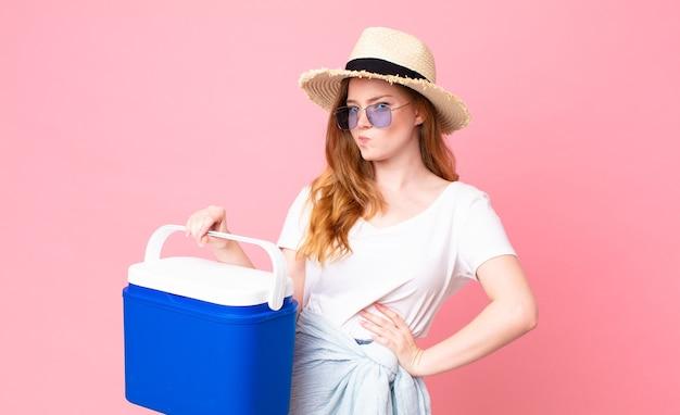 Mulher bonita ruiva dando de ombros, sentindo-se confusa e incerta e segurando uma geladeira portátil de piquenique