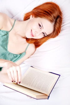 Mulher bonita ruiva de camisola branca deitada na cama e lendo o livro.