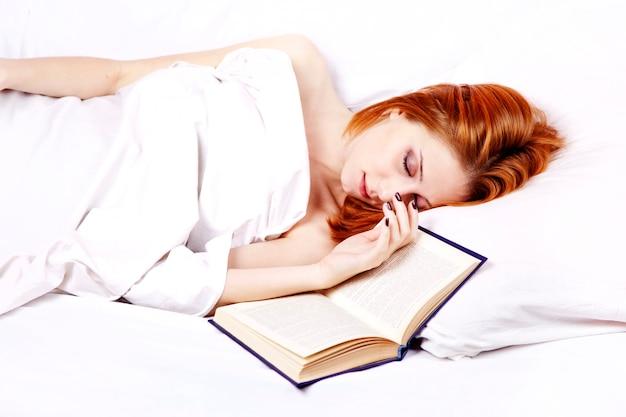 Mulher bonita ruiva de camisola branca, deitada na cama perto do livro.