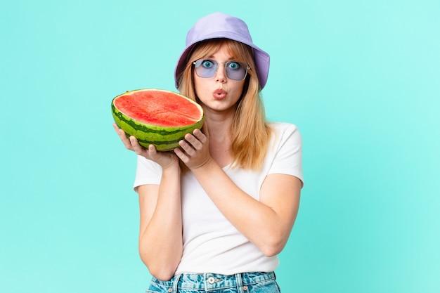 Mulher bonita ruiva e segurando uma melancia. conceito de verão