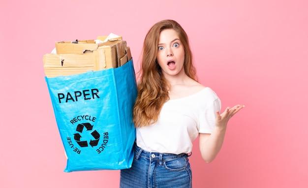 Mulher bonita ruiva extremamente chocada e surpresa segurando um saco de papel reciclado
