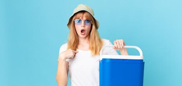 Mulher bonita ruiva olhando chocada e surpresa com a boca aberta, apontando para si mesma e segurando uma geladeira portátil. conceito de verão