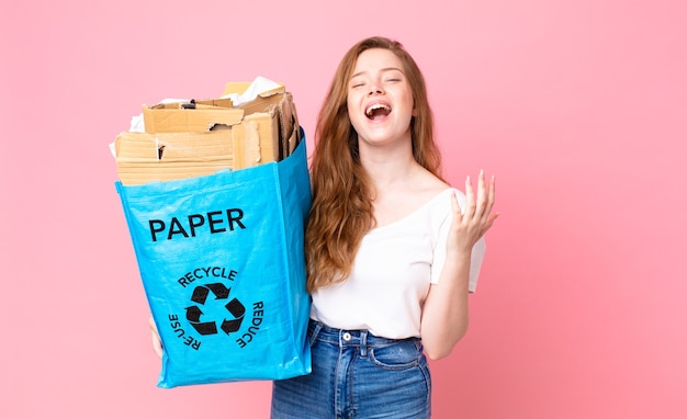 Mulher bonita ruiva parecendo desesperada, frustrada e estressada segurando um saco de papel reciclado