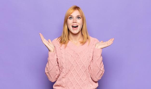 Mulher bonita ruiva parecendo feliz e animada, chocada com uma surpresa inesperada com as duas mãos abertas ao lado do rosto Foto Premium