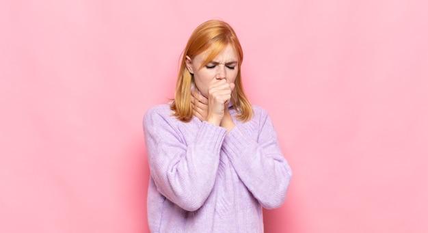 Mulher bonita ruiva passando mal com dor de garganta e sintomas de gripe, tosse com a boca coberta