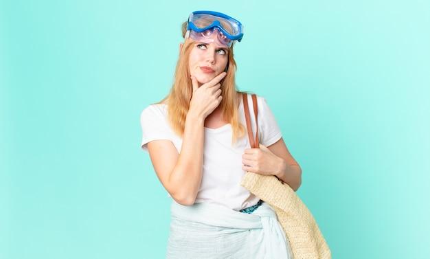 Mulher bonita ruiva pensando, sentindo-se duvidosa e confusa com óculos de proteção. conceito de verão