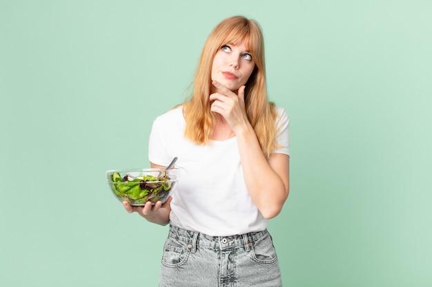Mulher bonita ruiva pensando, sentindo-se duvidosa e confusa e segurando uma salada. conceito de dieta