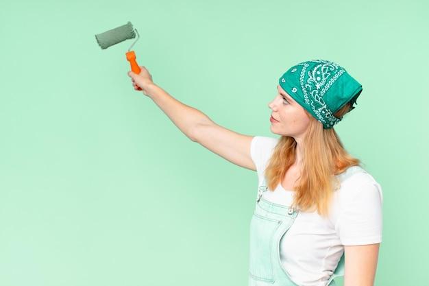 Mulher bonita ruiva pintando conceito de casa