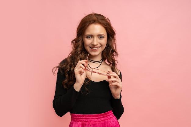 Mulher bonita ruiva posando sobre parede rosa. cabelos ondulados. sorriso perfeito.