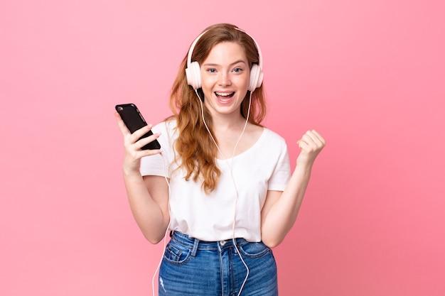 Mulher bonita ruiva se sentindo chocada, rindo e comemorando o sucesso com fones de ouvido e smartphone