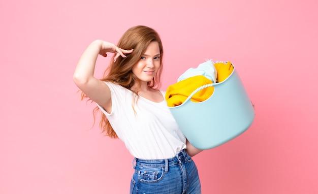 Mulher bonita ruiva se sentindo confusa e intrigada, mostrando que você é maluca e segurando um cesto de roupa suja