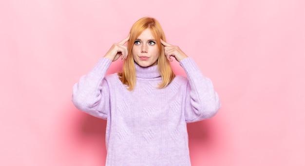 Mulher bonita ruiva se sentindo confusa ou duvidando, concentrada em uma ideia, pensando muito, procurando copiar o espaço ao lado