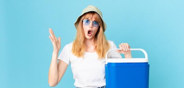 Mulher bonita ruiva se sentindo extremamente chocada e surpresa e segurando uma geladeira portátil. conceito de verão