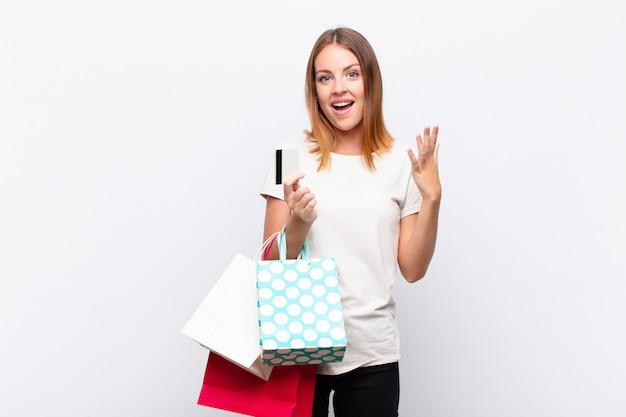 Mulher bonita ruiva se sentindo feliz, surpresa e alegre, sorrindo com atitude positiva, realizando uma solução ou ideia com sacolas de compras