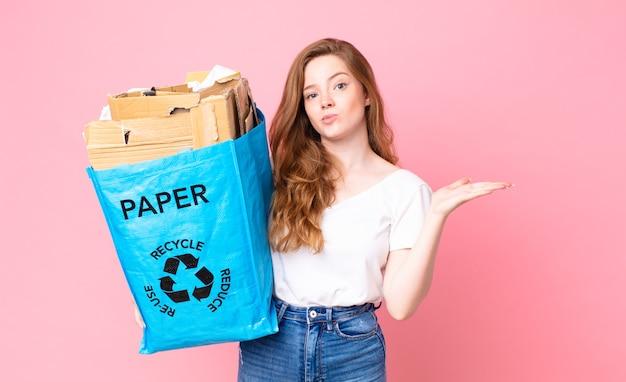 Mulher bonita ruiva se sentindo perplexa e confusa, duvidando e segurando um saco de papel reciclado