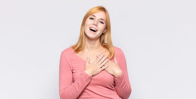 Mulher bonita ruiva se sentindo romântica, feliz e apaixonada, sorrindo alegremente e segurando o coração de mãos dadas