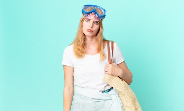 Mulher bonita ruiva se sentindo triste e chorona com um olhar infeliz e chorando com óculos de proteção. conceito de verão