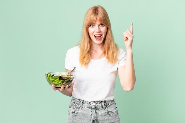 Mulher bonita ruiva se sentindo um gênio feliz e animado depois de perceber uma ideia e segurar uma salada. conceito de dieta