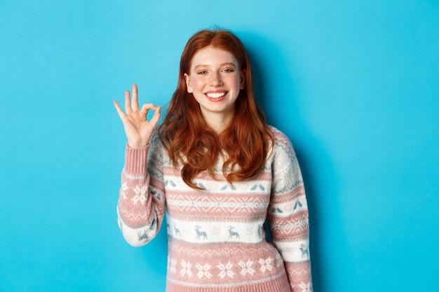 Mulher bonita ruiva sorridente mostrando sinal de tudo bem, elogiando o bom trabalho, gesto bem executado, em pé sobre um fundo azul.