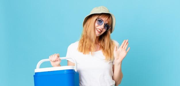 Mulher bonita ruiva sorrindo alegremente, acenando com a mão, dando as boas-vindas e cumprimentando você e segurando uma geladeira portátil. conceito de verão