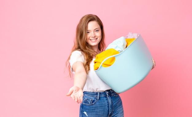 Mulher bonita ruiva sorrindo alegremente com simpática e oferecendo e mostrando um conceito e segurando uma cesta de lavagem com roupas