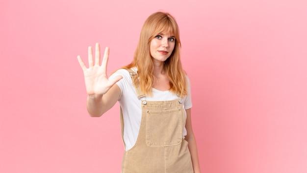 Mulher bonita ruiva sorrindo e parecendo amigável, mostrando o número cinco