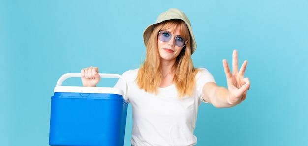 Mulher bonita ruiva sorrindo e parecendo amigável, mostrando o número três e segurando uma geladeira portátil. conceito de verão