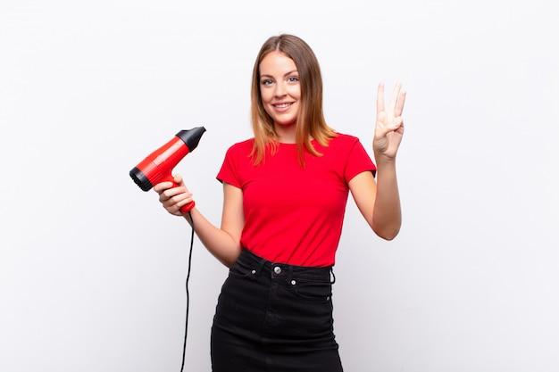 Mulher bonita ruiva sorrindo e parecendo amigável, mostrando o número três ou terceiro com a mão para a frente, em contagem regressiva segurando um cabeleireiro