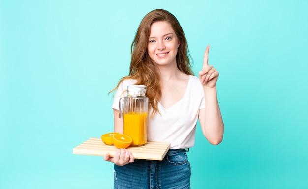 Mulher bonita ruiva sorrindo e parecendo amigável, mostrando o número um e segurando um suco de laranja