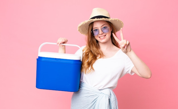Mulher bonita ruiva sorrindo e parecendo feliz, gesticulando vitória ou paz e segurando uma geladeira portátil de piquenique