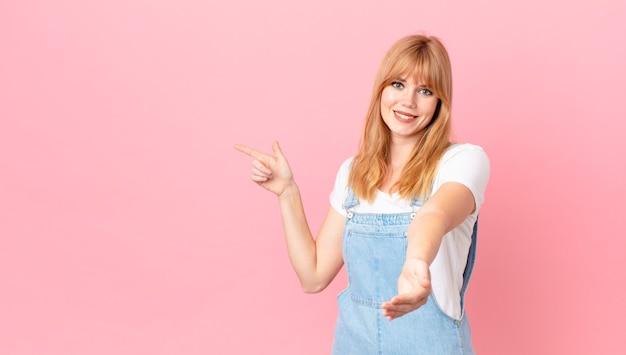 Mulher bonita ruiva sorrindo feliz com simpatia e oferecendo e mostrando um conceito