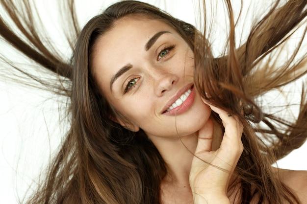 Mulher bonita sacode o cabelo no fundo branco