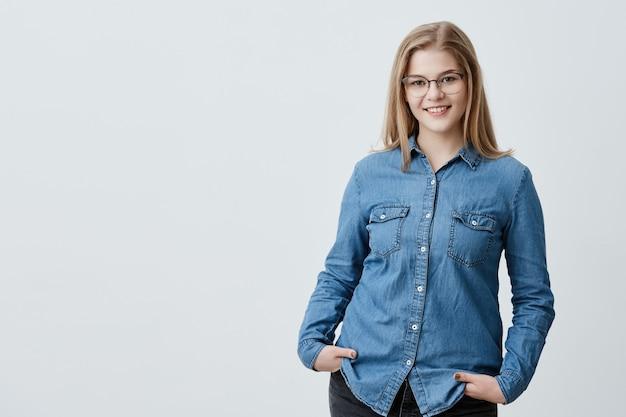 Mulher bonita satisfeita com cabelo loiro liso, olhos escuros, óculos elegantes e pele saudável, vestida com camisa jeans, de mãos dadas nos bolsos sorrindo. pessoas e estilo de vida