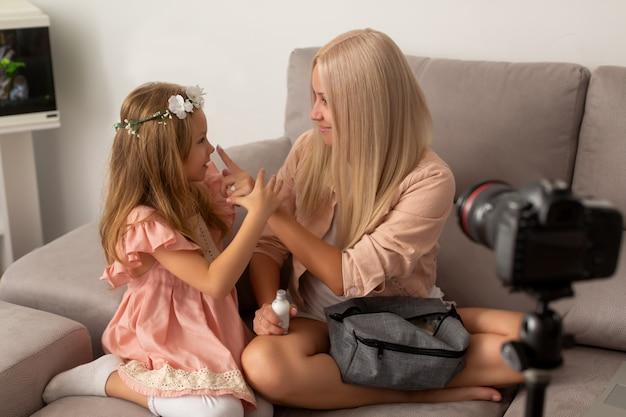 Mulher bonita se divertindo e colocando creme no nariz da filha sentado no sofá em casa