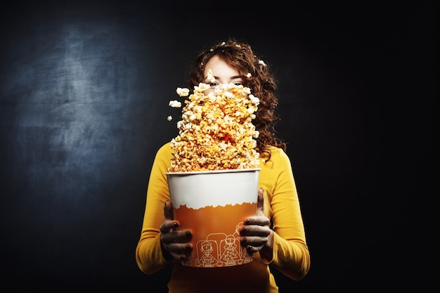 Mulher bonita se divertindo no cinema balançando balde de pipoca
