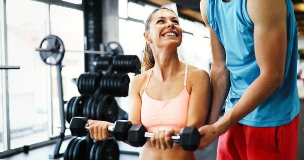 Mulher bonita se exercitando na academia com a ajuda de um personal trainer