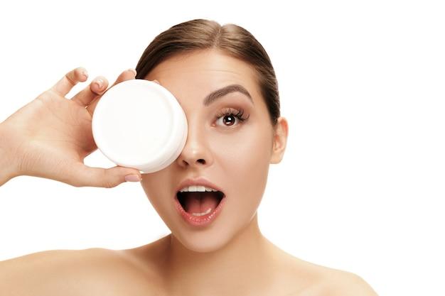 Mulher bonita se preparando para começar o dia aplicando creme hidratante no rosto