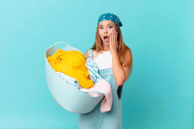 Mulher bonita se sentindo chocada e com medo segurando uma cesta de lavagem